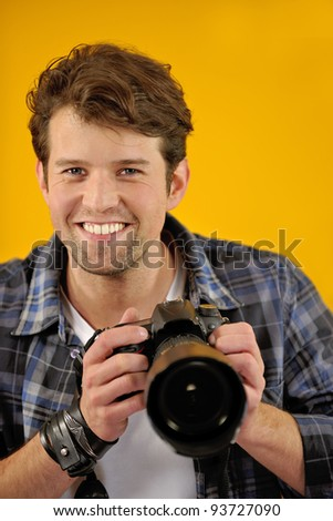 happy photographer with SLR camera on yellow background