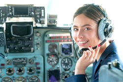 Happy pilot. Portrait of young pilot in uniform posing with a happy toothy smile with aircraft on the background. Female pilot smiles and wishes a successful flight