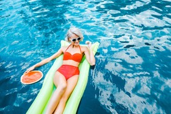 happy pin up girl in swimsuit relaxing on green inflatable mattress in swimming pool with watermelon