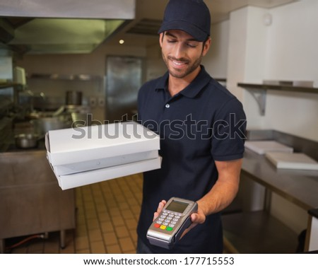 Happy pizza delivery man holding credit card machine in a commercial kitchen