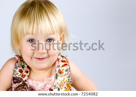 Happy playful blond kid with vivid blue eyes looking at you