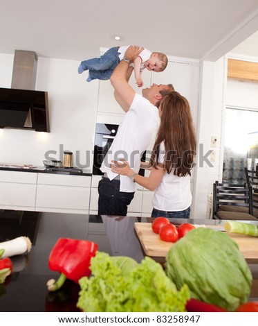 Happy playful family in kitchen - father mother and toddler son