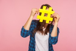 Happy playful girl in checkered shirt hiding behind yellow hashtag symbol, covering face with hash sign, concept of blogging and viral topics on internet. studio shot isolated on pink background