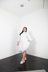 Happy playful plus size model in loose white dress posing in simple interior over white walls background for fashion campaign. Concept of body positivism and diversity. White Caucasian brunette female