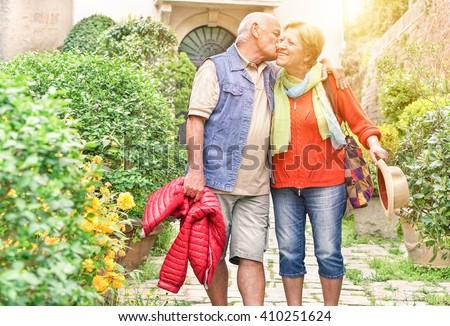 Happy playful senior couple in love tenderly enjoying romantic vacation for wedding anniversary celebration - Joyful elderly active lifestyle - Warm filter with artificial sunlight