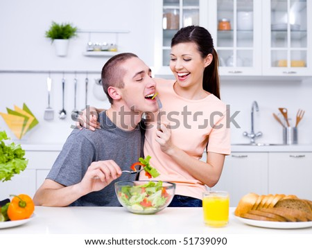 Happy playful young couple eating together in the kitchen - stock photo