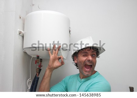 Happy plumber installing an electric water heater