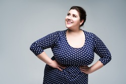 Happy plus size fashion model in blue polka dot dress, fat woman on gray studio background, body positive concept