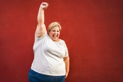 Happy plus-size woman celebrating and dancing for female power - Curvy overweight lady having fun with red background - Emancipation and confident concept - Focus on face
