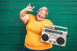 Happy plus-size woman dancing and listening rock music with vintage boombox - Emancipation and confident concept - Focus on face