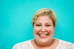 Happy plus-size woman portrait - Curvy overweight lady with turquoise background - Emancipation and confident concept - Focus on face