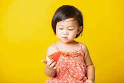 Happy portrait Asian baby or kid cute little girl attractive laugh smile wearing t-shirt playing holds cut watermelon fresh for eating, isolated on yellow background, healthy food and summer concept