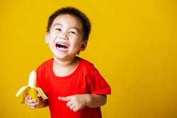 Happy portrait Asian child or kid cute little boy attractive smile wearing red t-shirt playing holds peeled banana for eating, studio shot isolated on yellow background