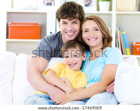 Happy portrait of beautiful smiling family with little son - indoors - stock photo