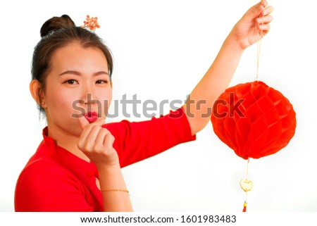 happy portrait of young beautiful and sweet Asian Chinese woman in traditional bun hair style and red dress holding lantern doing love fingers sign celebrating New Year in China