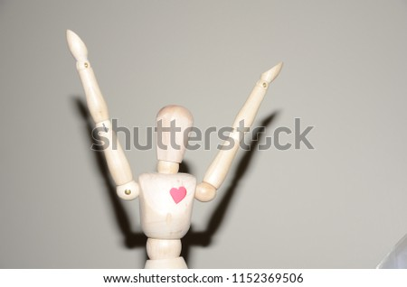 Happy pose of a wooden manikin with a simple heart shape on its chest #1152369506