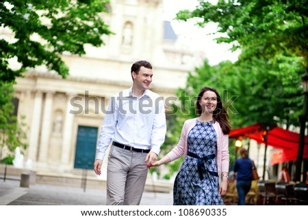 Happy positive couple walking in Paris near a street cafe