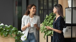 Happy positive female colleagues joking laughing during coffee break in work space, smiling diverse women business team talking having fun enjoy conversation good friendly relations walking in office