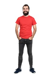 Happy positive friendly bearded man in red t-shirt and tight jeans laughing at camera. Full body length portrait isolated over white studio background.