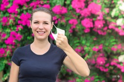Happy positive girl, young beautiful woman takes off protective sterile medical mask from face outdoors, smiling. Happy end. Pollen allergy. Victory over coronavirus. Pandemic Covid-19. Spring flowers