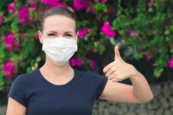 Happy positive girl, young cheerful beautiful woman in protective sterile medical mask on her face looking at camera outdoors, smiling, show thumb up, like gesture. Happy end. Pollen allergy