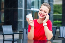 Happy positive girl, young cheerful woman in red smiling, relaxing, enjoying conversation, chatting, talking on cell mobile phone, coffee to go, laughing, sitting in cafe on terrace, having good time