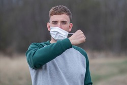 Happy positive guy, young man takes off or takes on protective sterile medical mask from face outdoors, smiling. Happy end of quarantine. Victory over coronavirus. Pandemic Covid-19