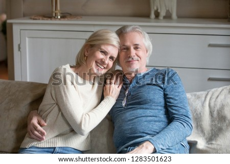 Happy positive mature retired couple sitting on couch in cozy living room, loving husband cuddle beloved wife aged people smiling looking posing for camera feeling good and comfort at modern warm home