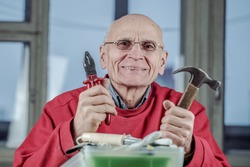 Happy positive senior man in glasses holds hammer and pliers in hands sitting at table of workroom