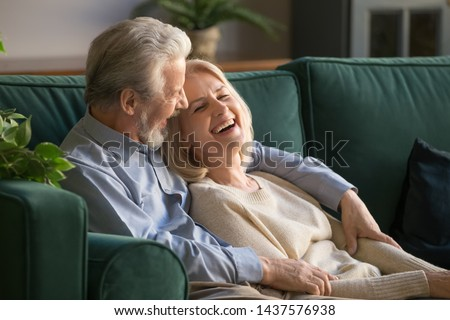 Photo of Happy positive senior old couple bonding embracing relaxing sit on sofa, cheerful loving elder husband and middle aged wife talking laughing resting having fun enjoying time together at home