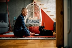 Happy positive senior woman sitting on the floor at home on yoga mat and practicing yoga with her dog.