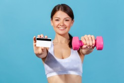 Happy positive woman athlete holding and showing credit card and dumbbell looking at camera with smiling, buying gym membership or private coach. Indoor studio shot isolated on blue background