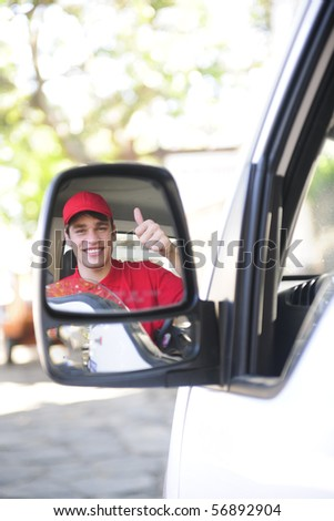 happy postal delivery courier in a van, rear view mirror perspective