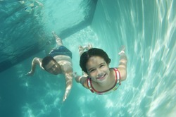Happy preadolescent daughter and father swimming underwater in pool