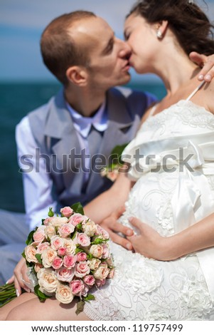 Happy pregnant bride and groom holding wedding bouquet posing against the sea. The groom tenderly embraces the pregnant belly of his wife.
