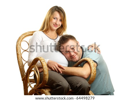 Happy pregnant couple in cain chair isolated on white