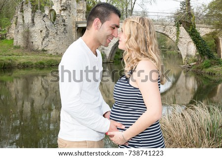 Happy pregnant family having fun and kiss in summer nature #738741223