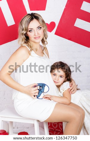 happy pregnant mother and her daughter - stock photo