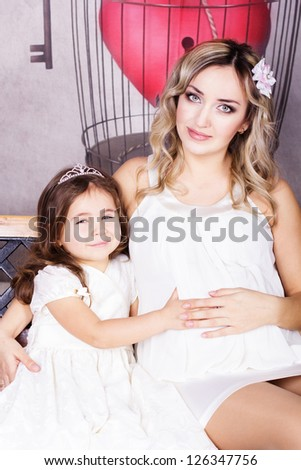 happy pregnant mother and her daughter