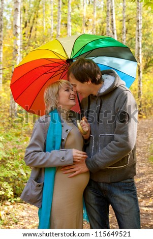 Happy pregnant woman and a man walking in the autumn forest under a rainbow colorful umbrella and kissing - stock photo