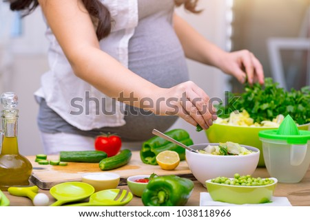 Happy pregnant woman cooking at home, doing fresh green salad, eating many different vegetables during pregnancy, healthy pregnancy concept