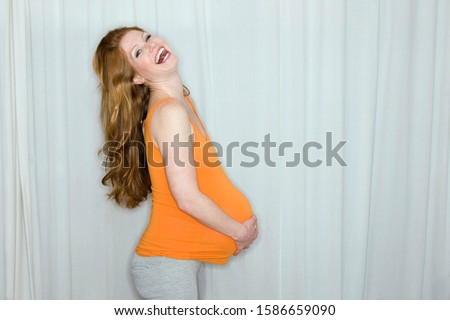 Happy pregnant woman holding her stomach