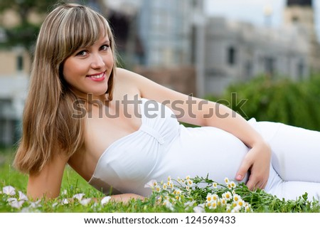 Happy pregnant woman in the park outdoors