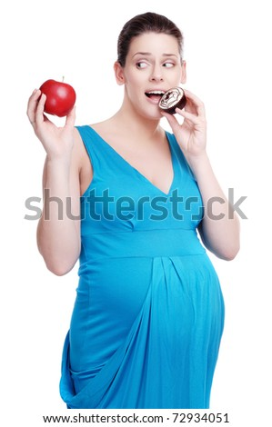 Happy pregnant woman making a choice between cake and apple