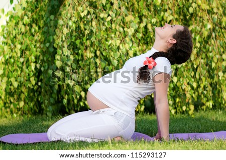 Happy pregnant woman relaxing in the park outdoors