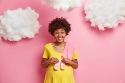 Happy pregnant woman with Afro hair holds baby socks over tummy prepares to give birth isolated over pink background. Expectant female going to have daughter soon. Pregnancy love maternity concept