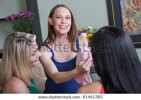 Happy pregnant woman with friends holds new baby clothes