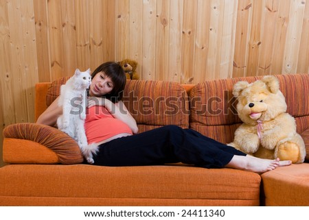 Happy pregnant young woman with cat sitting on the sofa #24411340