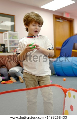 Happy preschool age boy enjoying different indoors activities and throwing colorful plastic balls inside a basket at an indoor playground with toys for children