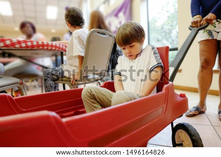 Happy preschool age boy riding a small red wagon and enjoying different indoors activities at an indoor playground with toys for children